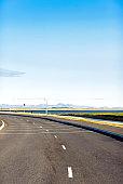 Empty winding street against blue sky in Iceland