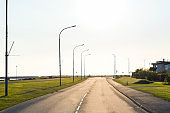 Empty road with street lights against sky.