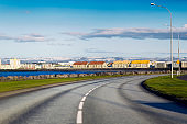 Empty Icelandic road with houses in background