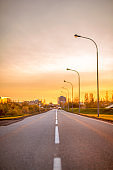 Empty road with street lights during sunset