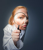 Portrait of scientist looking through magnifying glass