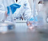 Chemist filling vials in experiment at laboratory