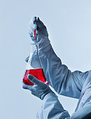 Male chemist holding red chemical in beaker