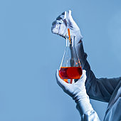 Chemist holding orange chemical in flask in pipette