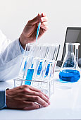 Chemist pouring blue medical solution in test tube