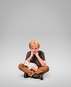 Portrait of boy with rabbit over gray background