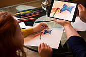 Mother showing tablet PC with drawing to daughter
