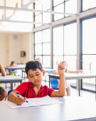 Boy writing on paper during exam in classroom