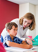 Young teacher assisting boy at desk in class