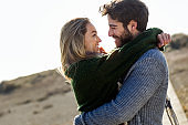 Happy young couple enjoying the day in a cold winter on the beach.