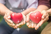 Family caregivers concept. Senior twin or two relatives, friends, or neighbors holding red heart shape for taking care each other in nursing home wellbeing service community.
