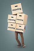 A man is carrying many moving boxes at once