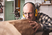 Mature carpenter working on a bandsaw