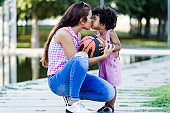 Beautiful young mother kissing her son in the park.