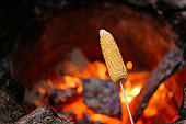 Summer food. Grilling corn on a stick, copy space.
