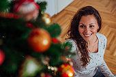 Beautiful happy woman decorating Christmas tree, close-up, portrait.