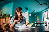 Positive woman eating salad at cozy cafe.