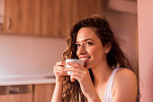 Close-up portrait of a young woman with curly hair drinking coffee at home.
