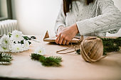 Unrecognizable woman in sweater decorating gifts in natural materials.