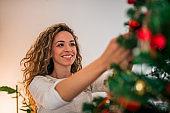 Smiling girl decorating Christmas tree, close-up.