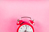 Small red alarm clock on bright pink table