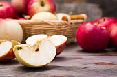 Sliced apple and ripe red apples on a wooden table and in a basket.