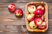 Fresh harvest of apples. Nature theme with red apples in a basket on a wooden background.