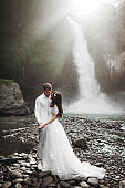 Young couple in love bride and groom, wedding day near a mountain waterfall.