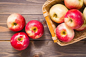 Ripe red apples and basket with apples on a wooden table