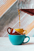 Pouring coffee on a cup on colorfull background