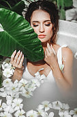 Woman relaxing in round outdoor bath with tropical flowers.