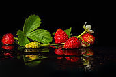 Sweet red berries, wild strawberries on a black background. Against the backdrop of a drop of water, a reflection. Selective focus, place for text.