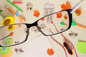 Look through glasses, stationery or school supplies. Selective focus in the foreground. Back to school concept. Copy space, top view, flat lay.