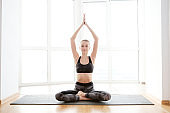 Skinny woman meditating in lotus pose in front of the window