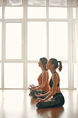 Two woman doing yoga flow in studio