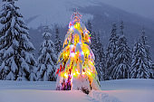 Fluffy Christmas tree with colorful garlands. Night winter mountain landscapes. Location the Carpathian, Ukraine, Europe.