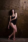 Young woman dancer. Young woman modern dancer. Skill ballet dancer posing. dancer posing near the wall. full length portrait of a flexible young woman posing near the wall. Dancer, flexibility