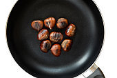 Chestnut on a black frying pan isolated on white background, top view. Roasted Chestnuts close up