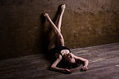 Theme is a sport and a beautiful sexy woman. Young caucasian girl lying on the floor kicking up posing in a black sports swimsuit clothes with bare feet on a dark wooden background in the studio