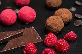 Theme sweet dessert cake handmade. Macro close-up dessert sweet candy round ball truffle set of black chocolate cocoa raspberry puer on a black background