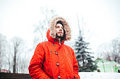 Portrait of a young stylish man with beard dressed in red winter jacket with hood and fur on his head stands against the backdrop of a snow-covered city and looks thoughtful. Winter and frost theme
