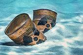Barrels with radioactive waste on ocean bottom underwater. 3D rendering