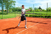 Young man training and playing tennis