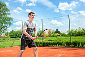 Young guy dressed in gray-black outfit holding a tennis racket