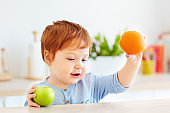 cute redhead toddler baby holding fresh apple and orange fruits