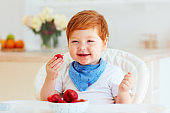 portrait of happy toddler baby eating tasty fresh strawberries