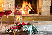 Two glasses of wine and christmas lantern near cozy fireplace, in country house.