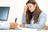 Unrecognizable female doctor prescribing a medicine for depressed female patient