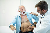 Doctor examining senior man's painful stomach.