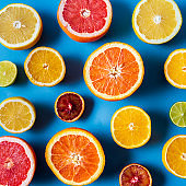 Flat lay the raw fresh citrus fruit - yellow and red orange fruit and lime leaves.